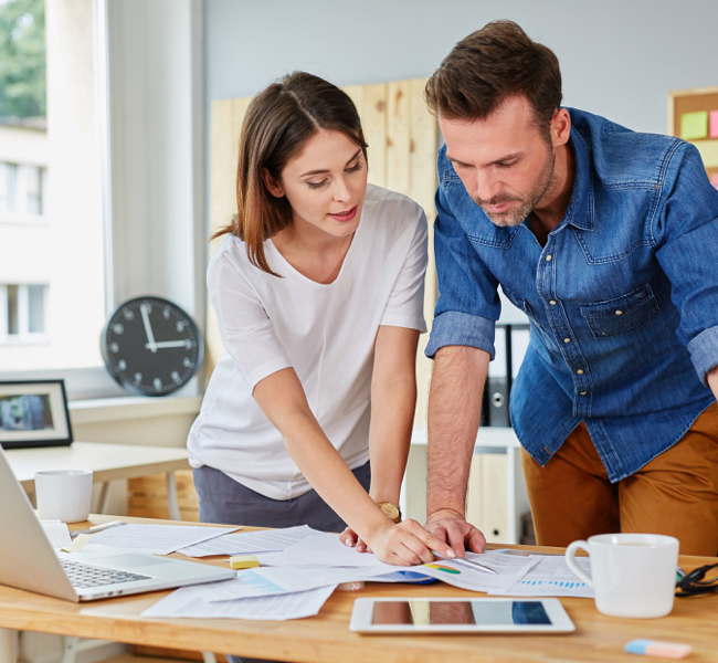 Man and woman looking at desk with images