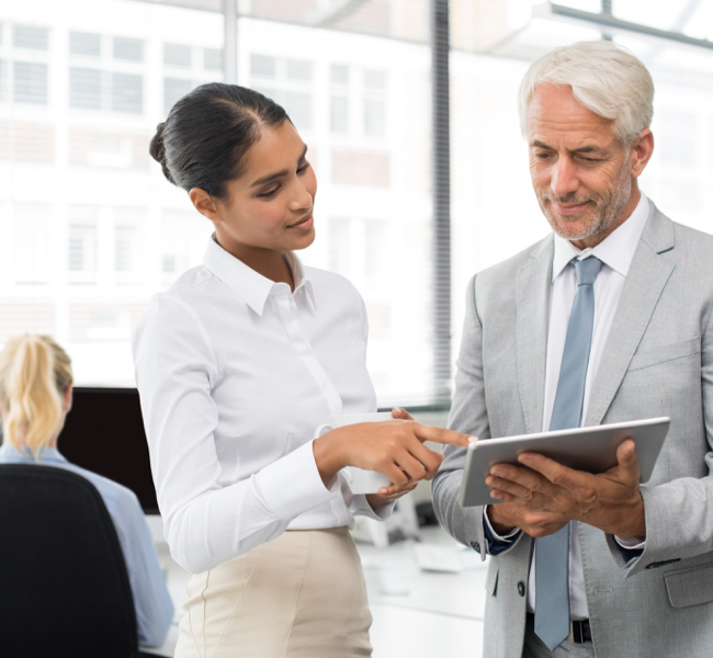 Woman pointing to tablet man is holding in business clothes