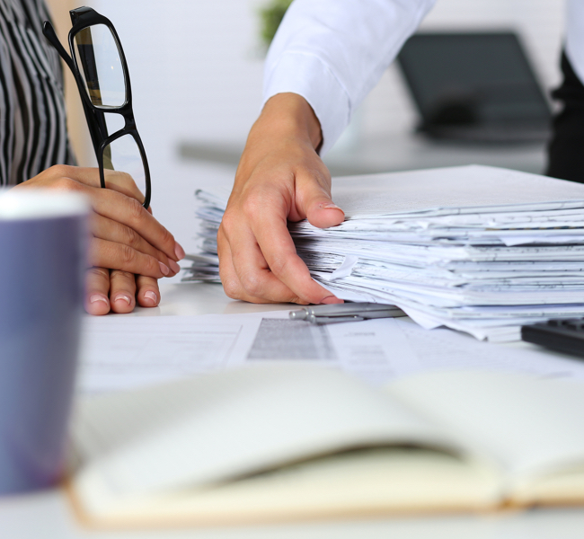 person grabbing tall stack of papers