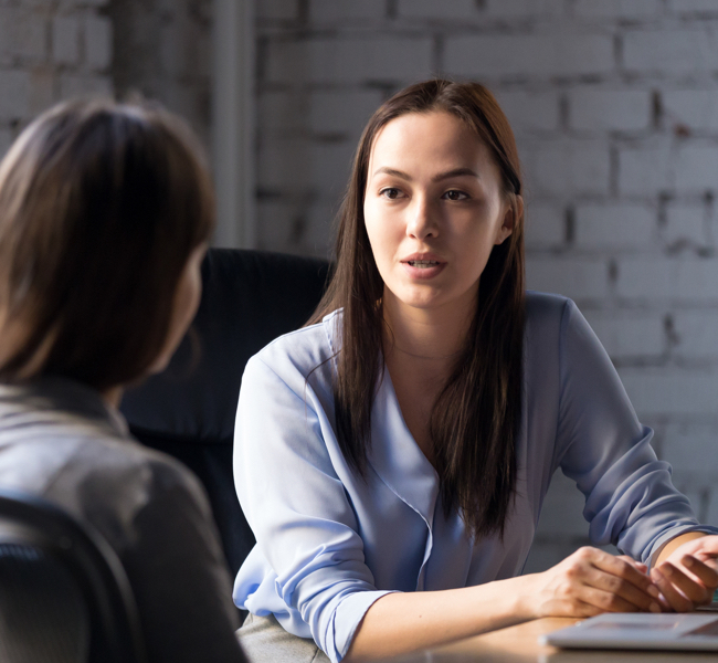 photo of woman sitting across table talking